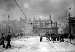 Civilians walking under damaged power lines after World War Two Air Raid in Liverpool